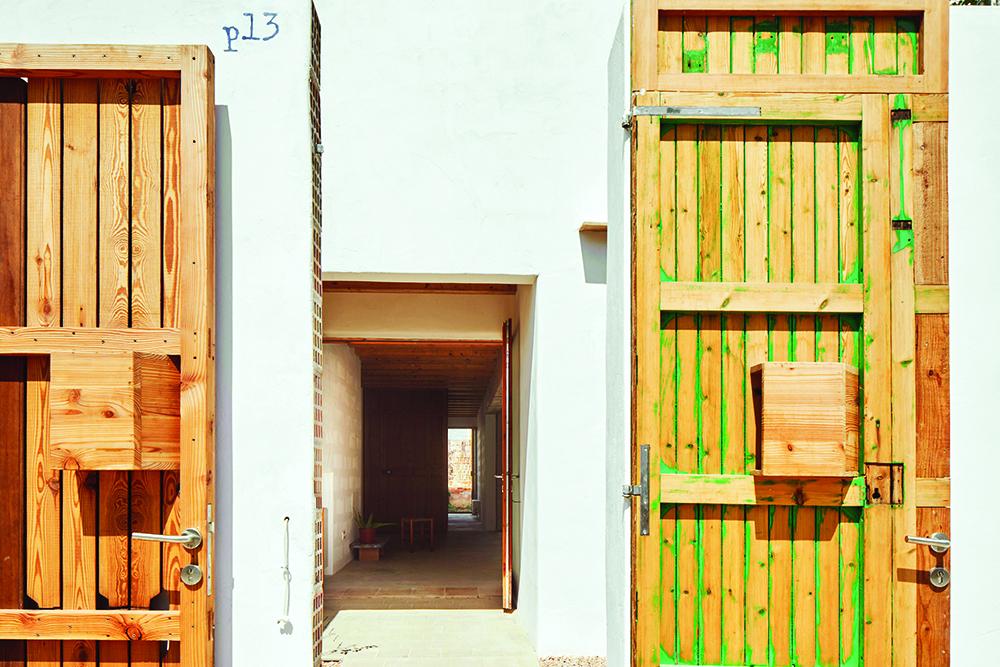 Figura 10: Acceso desde el espacio público.  Puertas reutilizadas con buzón incorporado.