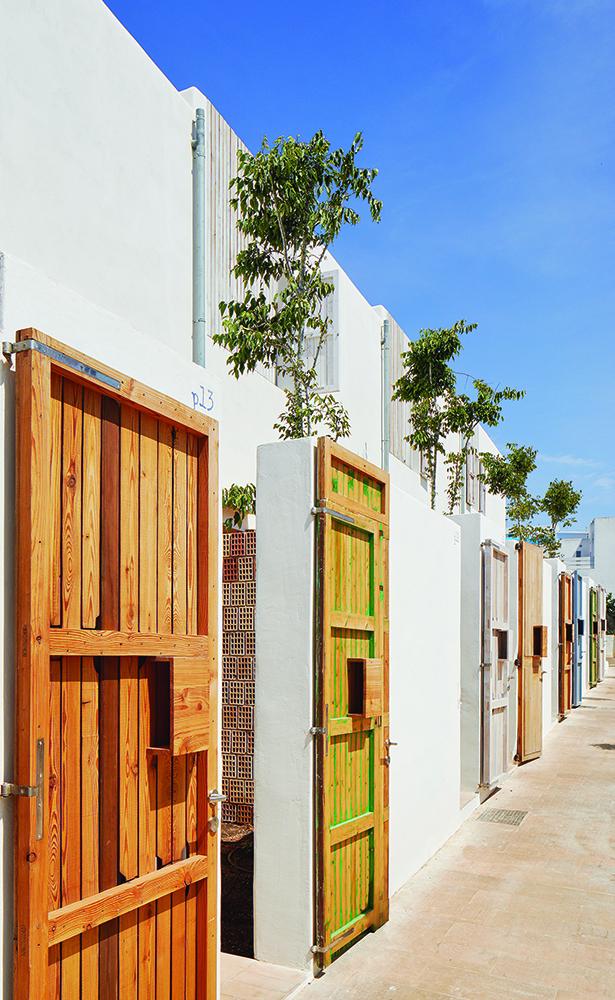 Figura 11: Patios de acceso en planta baja. Sombra de almez y muros permeables a la brisa marina.