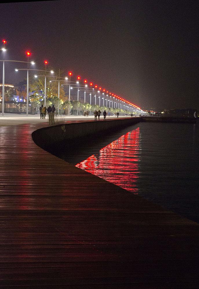 Figuras 18 y 19. A la izquierda, plataforma de madera sobre el rompeolas, de noche. Foto de Ioannis Kaktsis. A la derecha, paseando junto a la estatua de Alejandro Magno durante una noche de niebla. Foto de Konstantinos Koasidis.