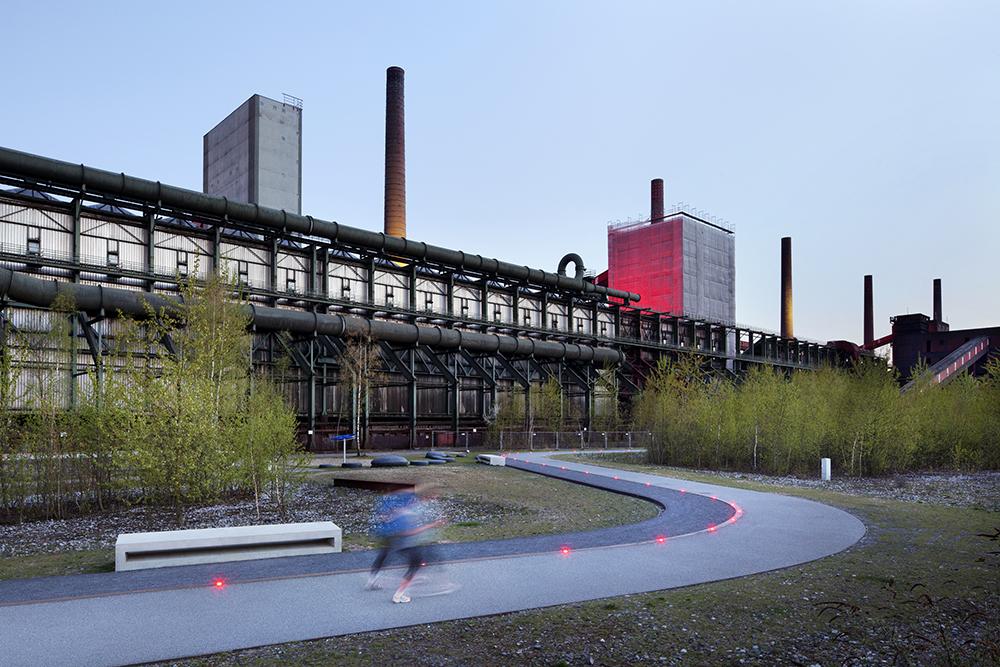 Figura 11. Norte de la batería de hornos de coque, el recorrido en zigzag del paseo mantiene a los visitantes cerca de la antigua sala de descarga. Grandes espacios abiertos en el bosque industrial abren la vista hacia la planta (© Claudia Dreyße, 2013)